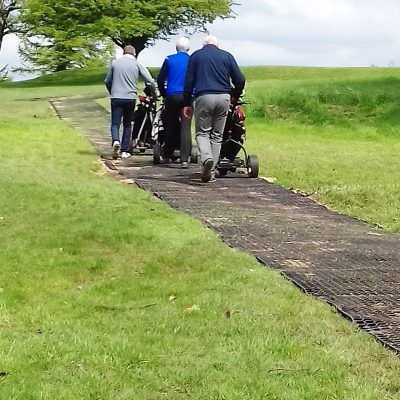 Golfers using rubber grass mat path